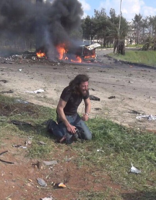 A Syrian videographer is left in tears by the sight of a child's charred body (Photo Twitter/Ala'a Shehabi)